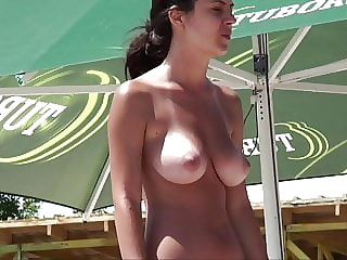 Topless brunette with nice tits on the beach