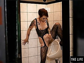 Girl pees and masturbates in a public mens room urinal